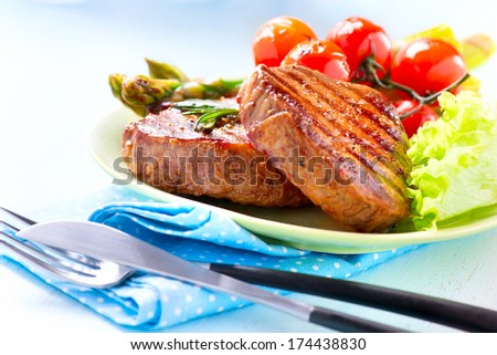 Steak. Grilled Beef Steak Meat with Vegetables - Asparagus, Cherry Tomato and Lettuce. Steak Dinner. Food  - stock photo