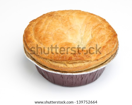 Steak meat pie in aluminium foil tray. Focus on centre of pastry top. - stock photo