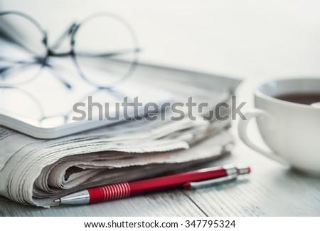 Steak of newspapers, eyeglasses and digital tablet - stock photo