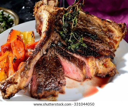 steak on a plate with grilled vegetables and sauce