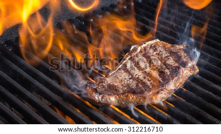 Steak on Grill with Flames and Room for Text - stock photo