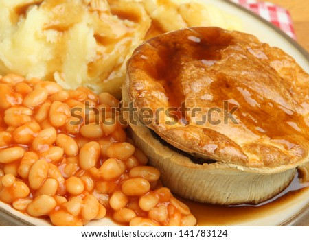 Steak pie with mashed potato and baked beans. - stock photo