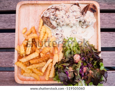 Steak pork with mushroom sauce, french fries and salad on wood plate.