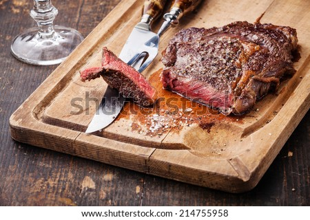 Steak Ribeye with knife and fork for meat on cutting board on dark wooden background - stock photo