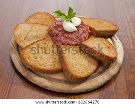 Steak tartar ready to eat on the wooden trencher - stock photo