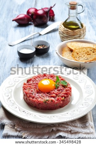 Steak tartar with egg yolk, red onion, capers, spicy sauce, sea salt, pepper and olive oil. - stock photo