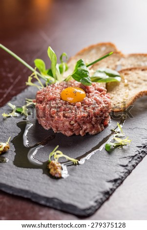 Steak Tartare with bread toasts served on a stone plate - stock photo