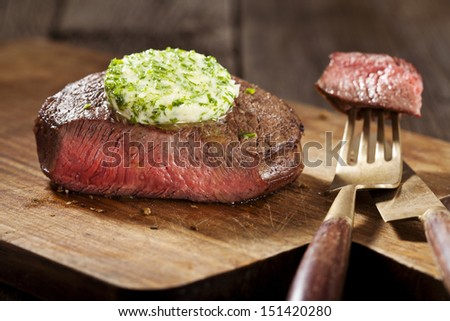 Steak with green butter on wooden board - stock photo