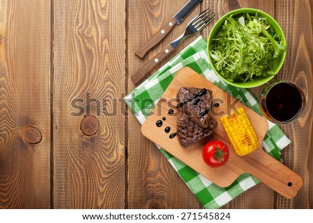 Steak with grilled corn, salad and red wine on wooden table. Top view with copy space - stock photo