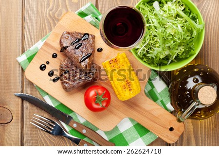 Steak with grilled corn, salad and red wine over wooden table. Top view - stock photo