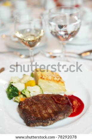 Steak with potato au gratin and vegetables on restaurant table