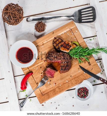 Steak with spices, thyme and chili served on a cutting board - stock photo