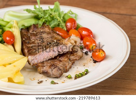 Steak with vegetable on wooden table