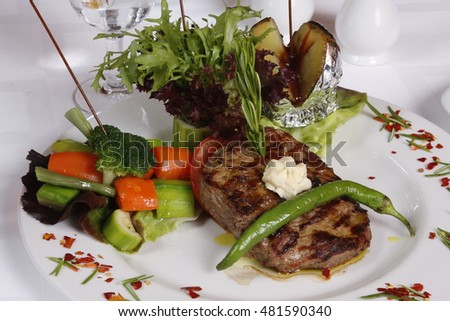 Steak with vegetables on the dinner plate.