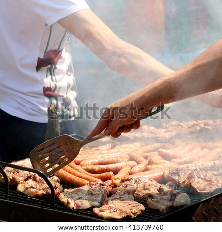 Steaks and sausages on the barbecue. Square format, selective focus.   - stock photo