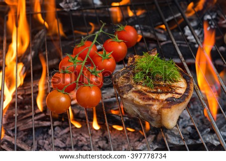 steaks and tomato on the hot flaming BBQ , picnic concept  - stock photo