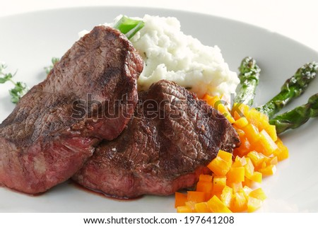 Steaks, mashed potatoes, peppers, and asparagus make an appealing dinner - stock photo