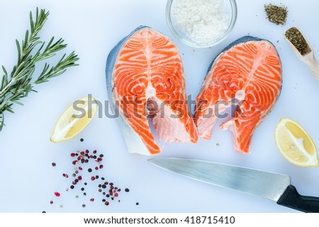 steaks of salmon with a sprigs of rosemary, lemon, pepper,  sea salt, olive oil and vinegar in glass jar, herbs in wooden scoop on a white cutting board on wooden background, top view. - stock photo