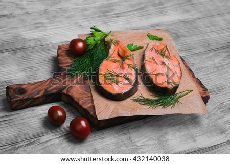 steaks salmon fish on a cutting board in special paper for steaks salmon fish, parsley, dill on light wooden background surface - stock photo