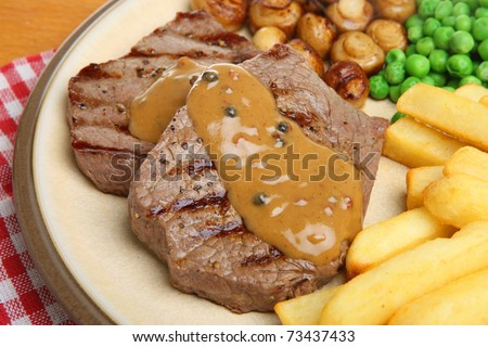 Steaks with peppercorn sauce, mushrooms, chips and peas. - stock photo