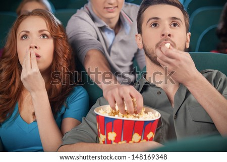 Stealing popcorn. Young men stealing popcorn during the movie session in cinema - stock photo