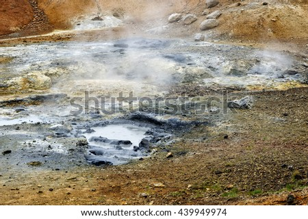 Steam and sulphur rise from a colorful hot spring on the surface of the earth in Iceland