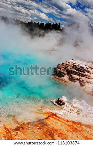Steam and wind create an otherworldly atmosphere at one of the many geyser pools at Yellowstone National Park in Wyoming (Excelsior Geyser). - stock photo