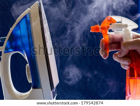 Steam created after a spray bottle has squirted water on a hot iron. - stock photo