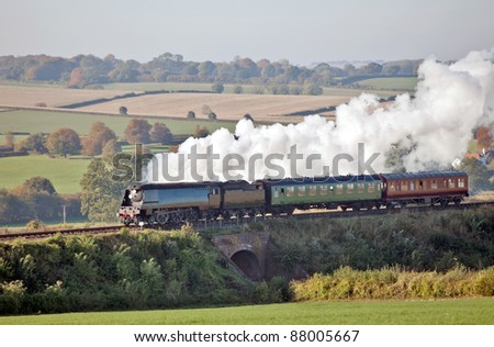 Steam dreams - steam train taking passengers on a journey through countryside on a warm autumns day - stock photo