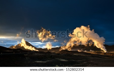 Steam erupting from geothermal power station at sunset, yellow light of setting sun back-lighting the columns of steam, Myvatn area, Iceland - stock photo