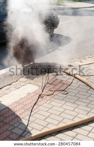 steam escaping from drain on street - stock photo