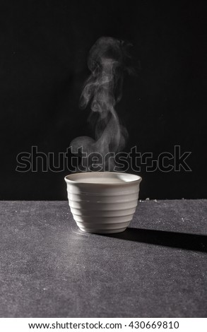 Steam from hot cup on black background