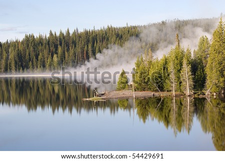 Steam from West Thumb geothermal features reflects in morning's light over Yellowstone Lake, Wyoming - stock photo
