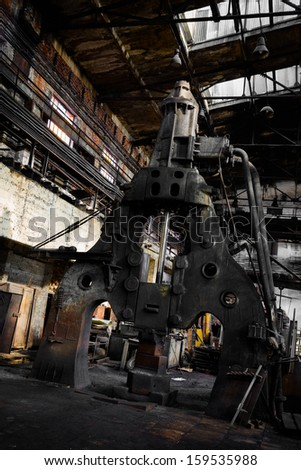 steam hammer in old iron factory - stock photo