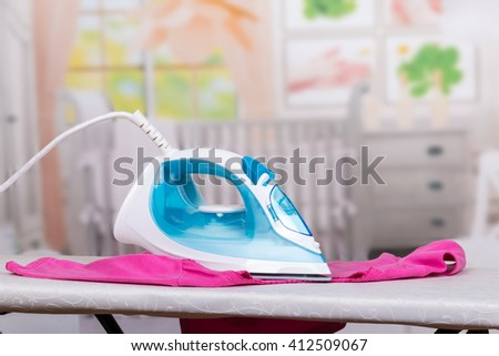 Steam iron, ironing board and clothes on the background of the room.