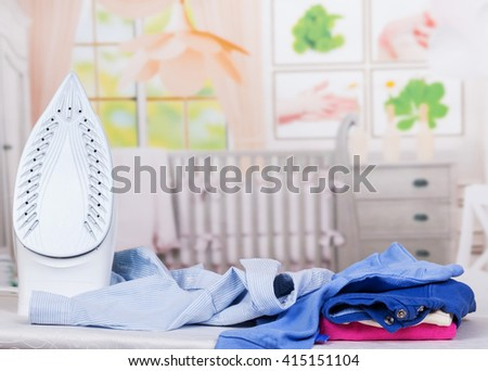 Steam iron, ironing board and clothes on the background of the room. - stock photo