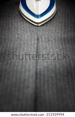 Steam iron on men's suit. - stock photo