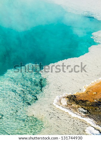 Steam rises from a beautiful deep blue hot spring pool at West Thumb Geyser Basin in Yellowstone National Park, Wyoming, USA. - stock photo