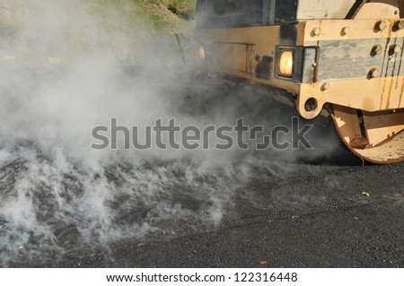 Steam rises from hot asphalt during construction of a new road - stock photo