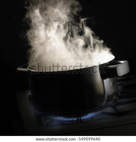 STEAM RISING FROM PAN OF WATER SIMMERING ON GAS COOKER