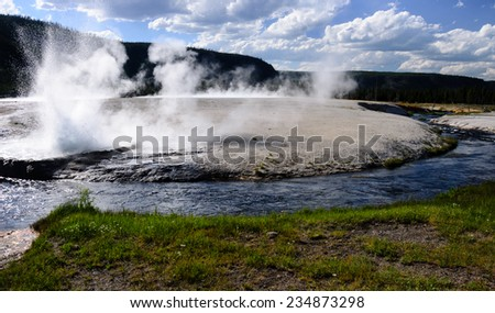 Steam rising over the hot river with erupting geyser in Yellowstone national park - stock photo