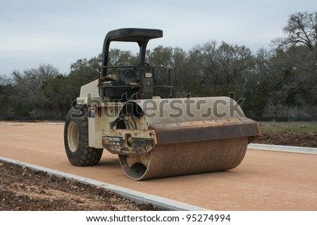 Steam Roller on road that is under construction - stock photo