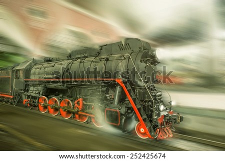 Steam train goes fast on the night station background. Vintage image. - stock photo