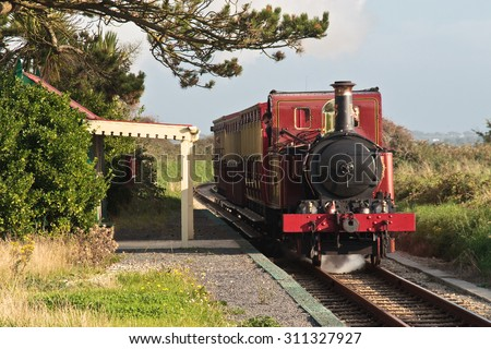 Steam train passing the tiny, rural Ballabeg Station, on the Isle of Man Steam Railway