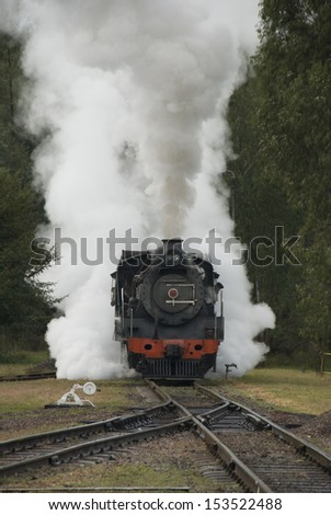 Steam train traveling along the railway line with steam bellowing out the sides and the top - stock photo