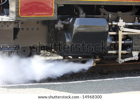 Steam train venting steam red and black