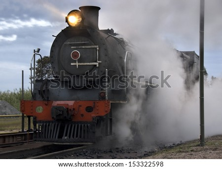Steam train warming up at the ash pits early on a winter morning - stock photo