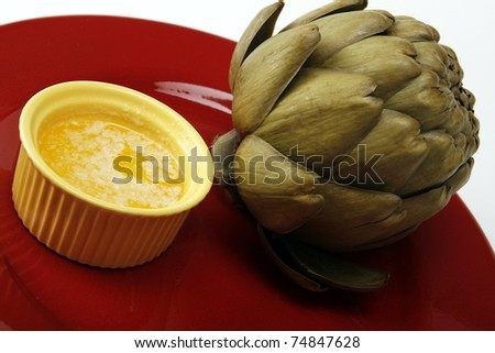 Steamed artichoke with melted butter on a red ceramic plate. - stock photo