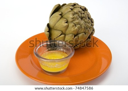 Steamed artichoke with melted butter on an orange ceramic plate. - stock photo
