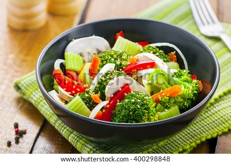 Steamed broccoli with onion, mushroom, carrot and pepper. Vegetable salad in bowl. International healthy vegetarian food. - stock photo